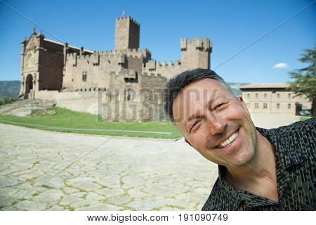 Happy smiling man making selfie over ancient spanish castle Javier, Navarre, Spain. Cultural and historical spanish heritage, architectural sight, wide angle, image toned