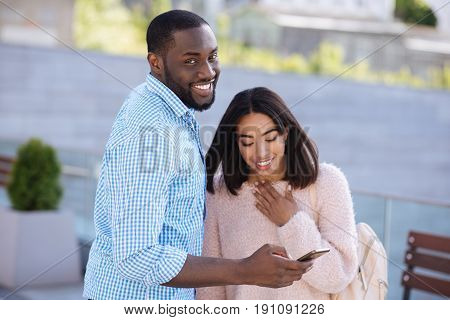 Sharing memories. Handsome intelligent young man using his smartphone for sharing some interesting picture his girlfriend enjoying