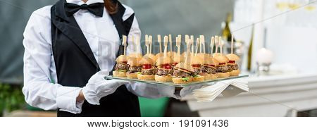 Catering service. Waiter carrying a tray of appetizers. Outdoor party with finger food, mini burgers, sliders