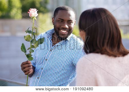 Gallant man. Goof looking genuine fun man asking a girl on a date and bringing pretty flower for her while trying making a good impression
