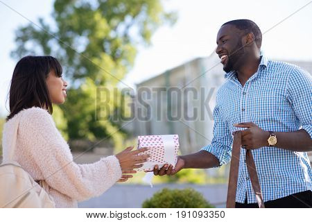 Exchanging gifts. Loving attractive devoted guy meeting his girlfriend and making her surprise gift as they celebrating their anniversary