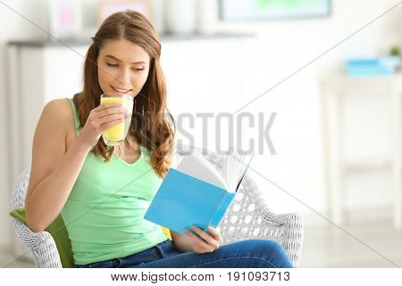 Weight loss concept. Beautiful young woman drinking healthy delicious smoothie and reading book at home