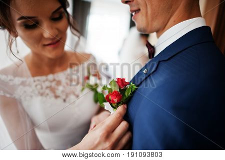 Gorgeous Bride Puts A Buttonhole Flower On A Groom's Jacket.