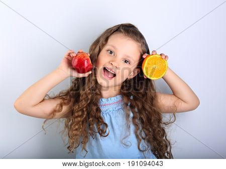 Cute joying grimacing happy kid girl with curly hair style holding citrus orange fruit and red apple in the hands in blue background