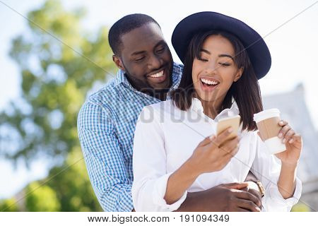 Just look at this. Classy modern elegant woman using her smartphone for sharing interesting things with her man as they having a date