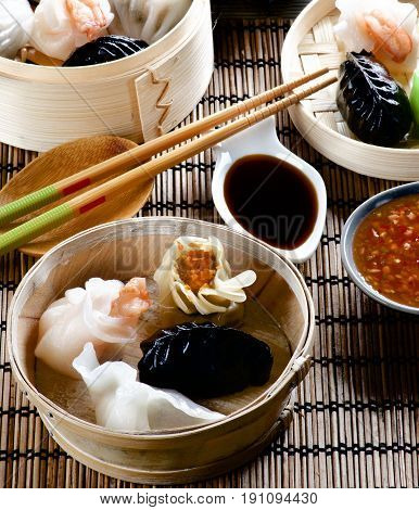 Assorted Dim Sum in Bamboo Steamed Bowls Red Chili and Soy Sauces with Chopsticks closeup on Straw Mat background