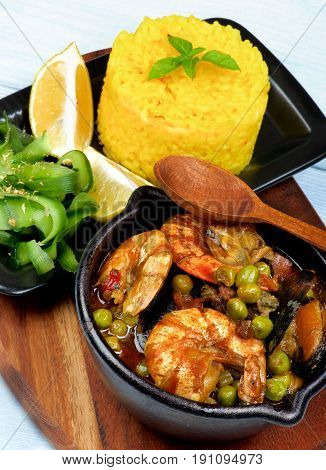 Delicious Seafood Curry with Saffron Rice Cucumber Salad and Lemon Served on Board closeup on Wooden background. Focus on Foreground