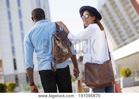 I got your back. Stylish happy modern people going for shopping together while heading to another mall and seeming excited
