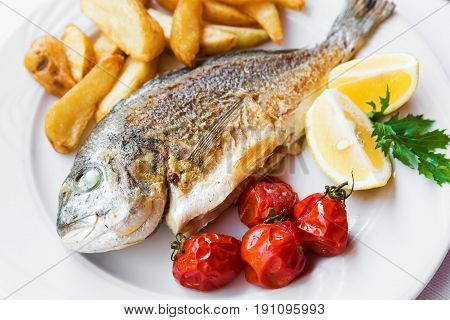 Fried Fish Dorado With Potatoes Chips, Fresh Herbs And Lemon