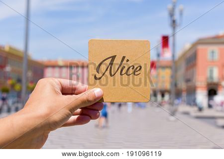 closeup of a young caucasian man holding a brown signboard with the word Nice written in it in front of the famous Place Massena square in Nice, France