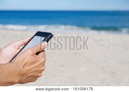 closeup of a young caucasian man reading in a tablet or e-reader on a white sand beach next to the sea