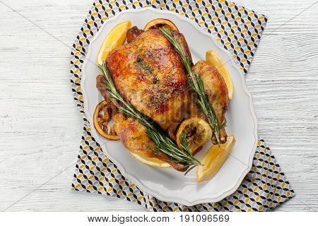 Homemade baked chicken with lemon and rosemary on table
