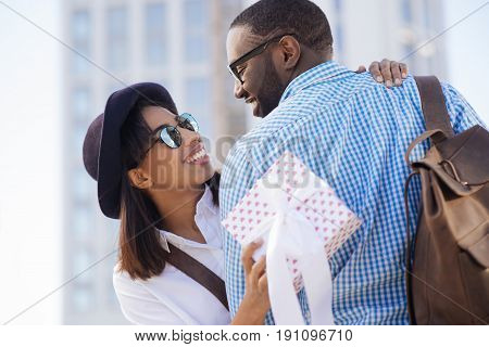 My perfect match. Fashionable unconventional delicate lady feeling happy while receiving little surprises from her boyfriend and hugging him