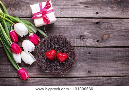 Decorative red little hearts in nest bright spring tulips flowers box with present on textured background. Selective focus. Place for text.