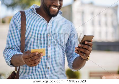 Worldwide shopping mall. Savvy young busy guy using his smartphone for buying goods online and paying for them with his credit card