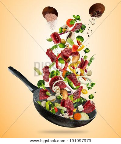 Fresh vegetables and pieces of beef meat flying into a pan, isolated on brown background. Concept of flying food, preparation, diet and healthy eating.