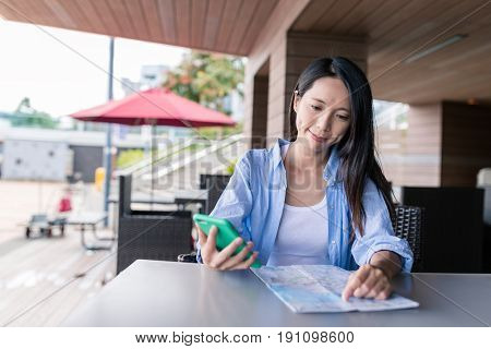 Woman use of mobile phone and city map in cafe
