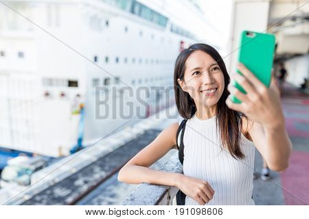 Woman taking selife by mobile phone in Cruise terminal