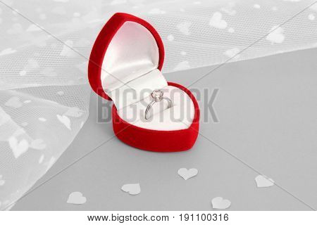 Red box with ring for marriage proposal on gray background