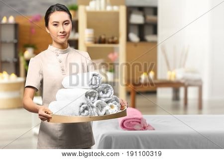 Young Asian masseur holding tray with towels in spa salon