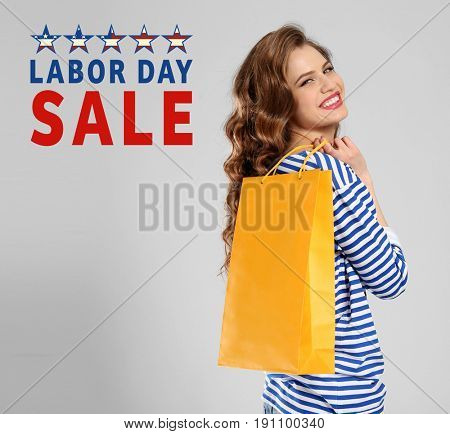 Concept of LABOUR DAY SALE. Woman with shopping bag on light background