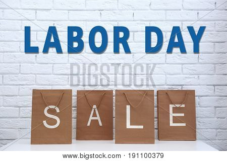 Concept of LABOUR DAY SALE. Shopping bags on white brick wall background