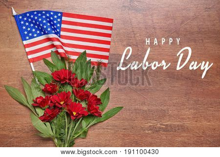 Text HAPPY LABOUR DAY with American flag and flowers on wooden background