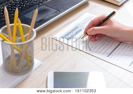 Filling in blank employment application form on a desk
