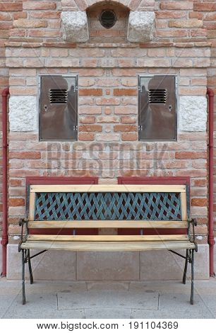 Old wooden bench outside with brick wall in background