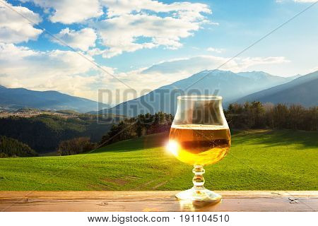 A glass of fresh beer on the background of the mountains