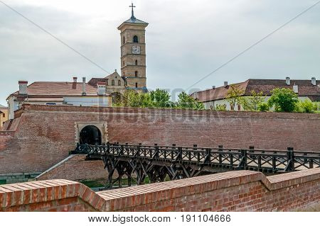 View at medieval fortress of Alba Iulia Transylvania Romania. Bridge of Gate nr 4 for enterance and Saint Michael Roman Catholic Cathedral in background.
