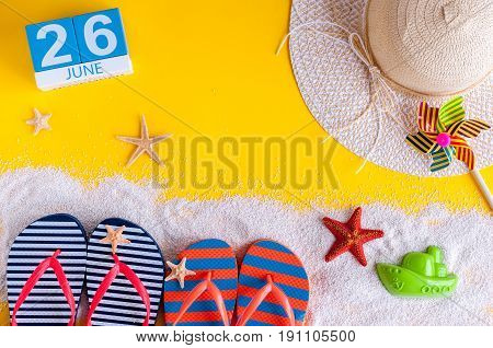 June 26th. Image of june 26 calendar on yellow sandy background with summer beach, traveler outfit and accessories. Summertime concept.