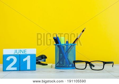 June 21st. Day 21 of month, calendar on yellow background with office suplies. Summer time at work. Go Skateboarding Day.