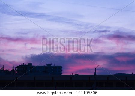 Colorful dawn/dusk sky over some buildings .