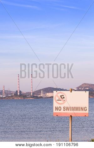 No Swimming Sign By The Beach, With Power Plant Station In The Background.