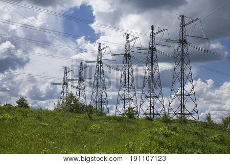 wide angle view of high voltage power pylons on against sky