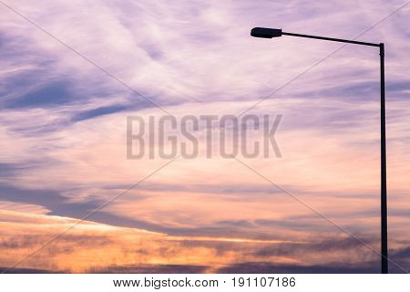 Street lamp silhouette on colorful dawn/dusk sky background.