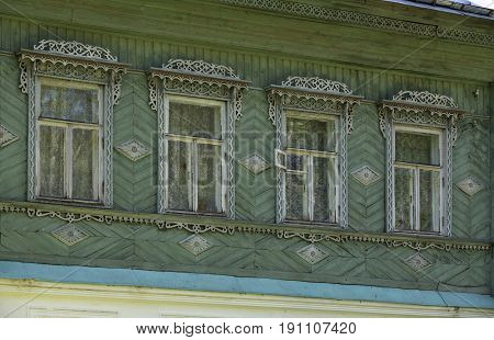 Facade of the old russian wooden house with windows and carved frames and pattern