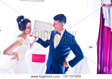 Beautiful Happy Wedding Couple Holding A Plate On Their Big Day In A Restaurant.