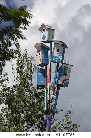 Lots of colorful nesting boxes on a pole