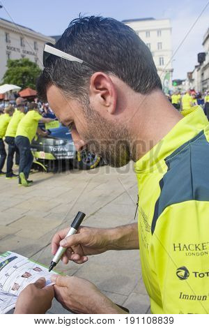 LE MANS FRANCE - JUNE 11 2017: Famous English racer Darren Turner gives autograph for fans Weighing administrative and technical checks of the race cars for competition 24 hours of Le mans circuit