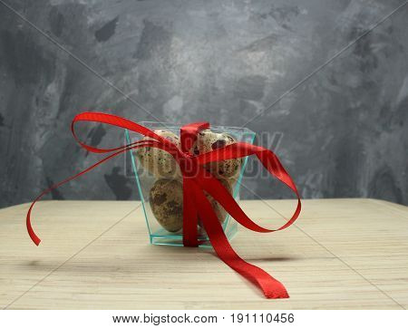 Quail eggs/ Quail eggs in box with red ribbon.