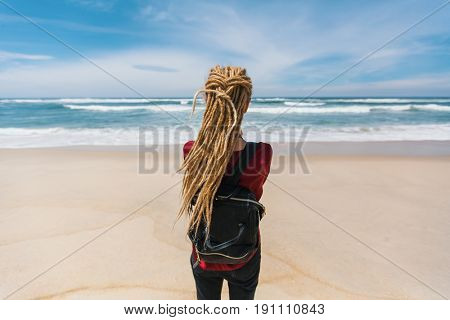 Young beautiful woman with blond dreadlocks is looking at the ocean. Rear view.