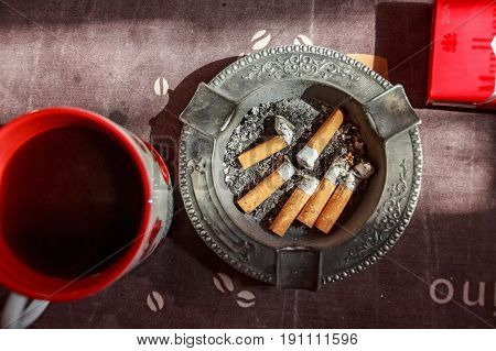 Various cigarette butts in full ashtray and a mug with tea on table