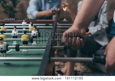 Close-up partial view of young people playing foosball indoors