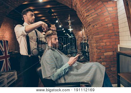 Side View Of Handsome Young Red Bearded Man Browsing At His Pda, While Getting A Haircut By Classy D