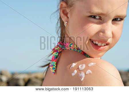 young girl applyng sun protector cream on her shoulder on the beach close to tropical turquoise sea under blue sky at sunny day