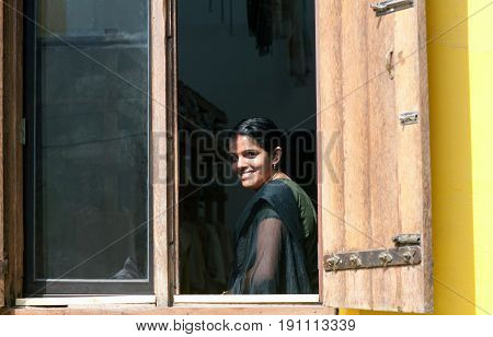 COCHIN, INDIA - JANUARY 21, 2016: Smiling beautiful Indian girl in sari looking outdoors through a window in Fort Cochin, Kerala, South India