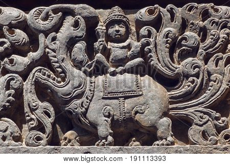Ancient Hindu god sitting on myth lion creature sculpured stone relief carvings from the 12th century temple's wall, Halebidu town of Karnataka. Old Indian artwork.