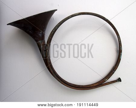 old darkened antique brass hunting horn on a white background